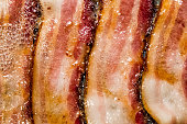 A macro view of bacon cooking on the stove.