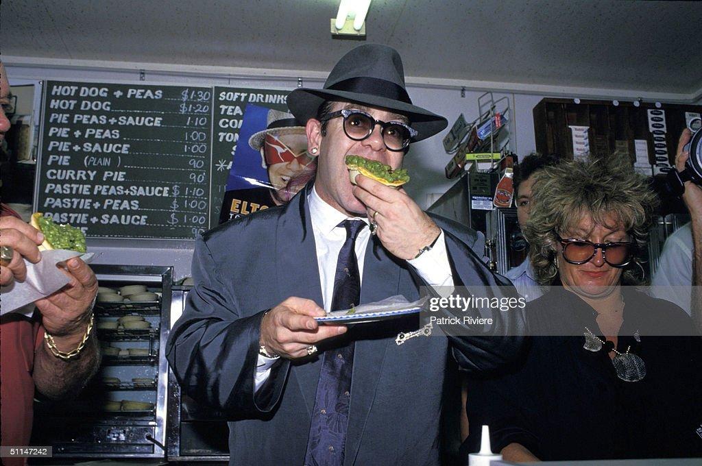 ELTON JOHN AT THE HARRY CAFE DE WHEELS IN SYDNEY EATING A HOMEMADE PIE.
