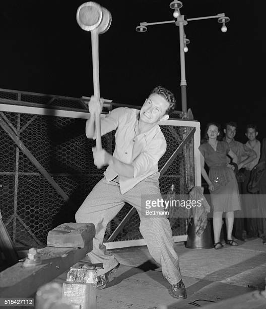 CONEY ISLANDNY'HIT THE BELL AND WIN A CIGAR' WHILE THE ADMIRING GIRL FRIEND STANDS BY A STALWART SWAIN SWINGS THE HEAVY SLEDGE HAMMER OTHER...