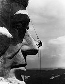 TOURISTS NEVER SEEE MOUNT RUSHMORE FROM THE TOP LOOKING MORE LIKE A PESKY FLY THAN A REPAIRMAN MIKE O'MERA CHECKS LINCOLN'S NOSE FOR CRACKS IN THE...