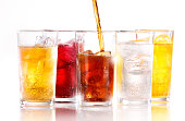 A row of five soft fizzy drinks, with one still being poured.  Drinks are shot with ice and are shot on white reflective background