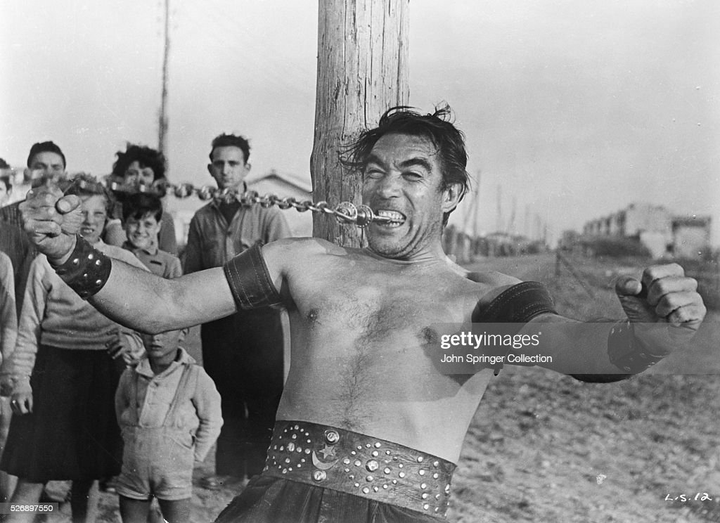 STRONGMAN ANTHONY QUINN EXHIBITS HIS STRENGTH BY PULLING A WEIGHT WITH HIS TEETH. A PONTI-LAURENTIIS PRODUCTION, DIRECTED BY FEDERICO FELLINI, 'LA STRADA' (THE ROAD). MOVIE STILL, 1954.