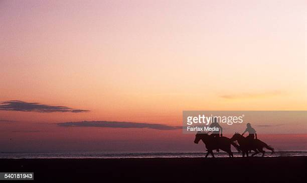 TWO PEOPLE RIDE HORSES ALONG THE BEACH AT SUNSET IN BALI