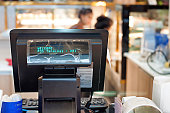 CASHIER DESK WITH POS COMPUTER TERMINAL IN SHOP, SELECTIVE FOCUS AND BLURRLY BACKGROUND
