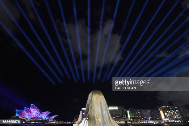A visitor takes pictures as Sydney's landmark Opera House is lit up with lights on the first day of the light festival 'Vivid Sydney' on May 26 2017...