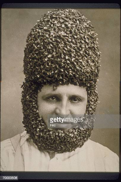 MAN SPORTS A BEEHIVE HAIRDO AND BEARD MADE OF ACTUAL BEES, C. 1940.