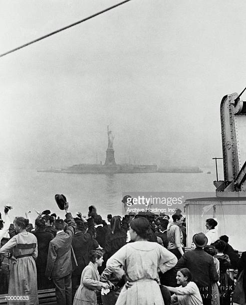 ELLIS ISLAND VIEW, DECK OF SHIP PULLING INTO NEW YORK HARBOR, C. 1900