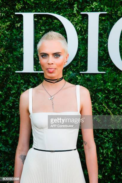 British model and actress Cara Delevingne sticks her tongue out as she poses while arriving for the opening of the Dior exhibition that celebrates...
