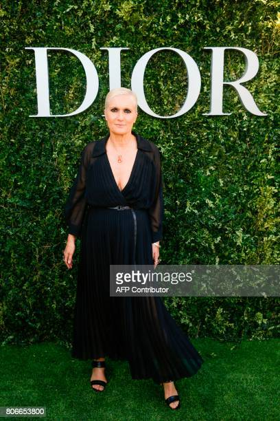 Italian fashion designer Maria Grazia Chiuri poses as she arrives for the opening of the Dior exhibition that celebrates the seventieth anniversary...