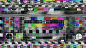 A TV test pattern or test card suffers digital glitch interference. Techniques used included databending and datamoshing