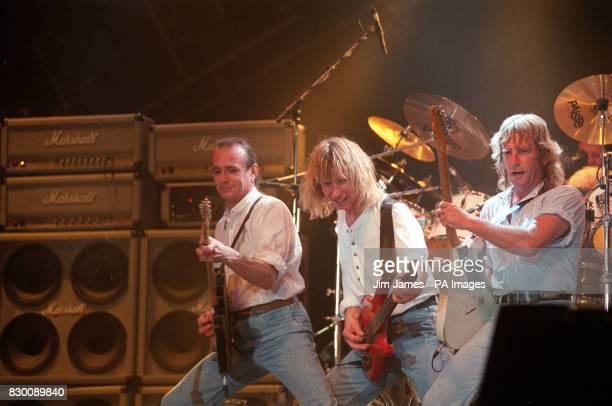 PHOTO 22/9/91 'STATUS QUO' JOHN EDWARDS RICK PARFITT AND FRANCIS ROSSI ON STAGE AT WEMBLEY ARENA