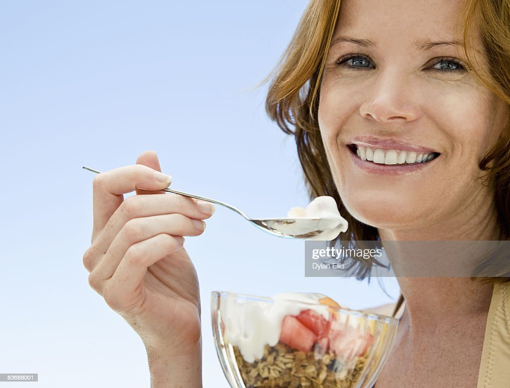 YOUNG WOMAN EATING HEALTHY FRUIT BREAKFAST BY POOL : Stock Photo