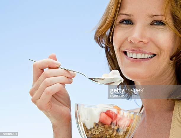 YOUNG WOMAN EATING HEALTHY FRUIT BREAKFAST BY POOL