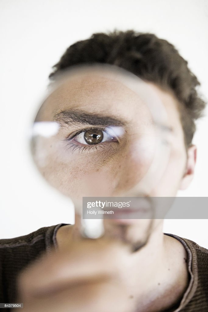 MAN LOOKING THROUGH A MAGNIFYING GLASS : Stock Photo