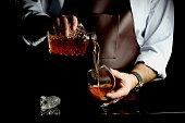 мужчина наливает коньяк в бокал за барной стойкой