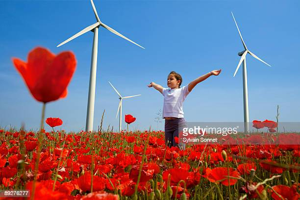 YOUNG GIRL WITH OUTSTRETCHED ARMS BY WIND TURBINES