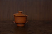 Clay Chinese tea set composed of cup, lid, saucer placed on the wood table in front of brown wood wall.'n