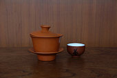 Clay Chinese tea set composed of cup, lid, saucer with 2 small tea cups are placed on the wood table in front of brown wood wall