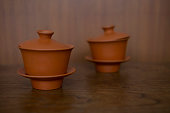 Two chinese tea sets made from clay composed of cups, lids and saucers, focus at the front one. They are set on the wood table in front of  wood wall.
