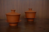 Two Chinese tea sets made from clay composed of cups, lids and saucers, focus at the back one. They are set on the wood table in front of  wood wall.