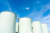 SILOS IN INDUSTRIAL FACTORY , CLEAR BLUE SKY CLOUD SUNNY DAY BACKGROUND