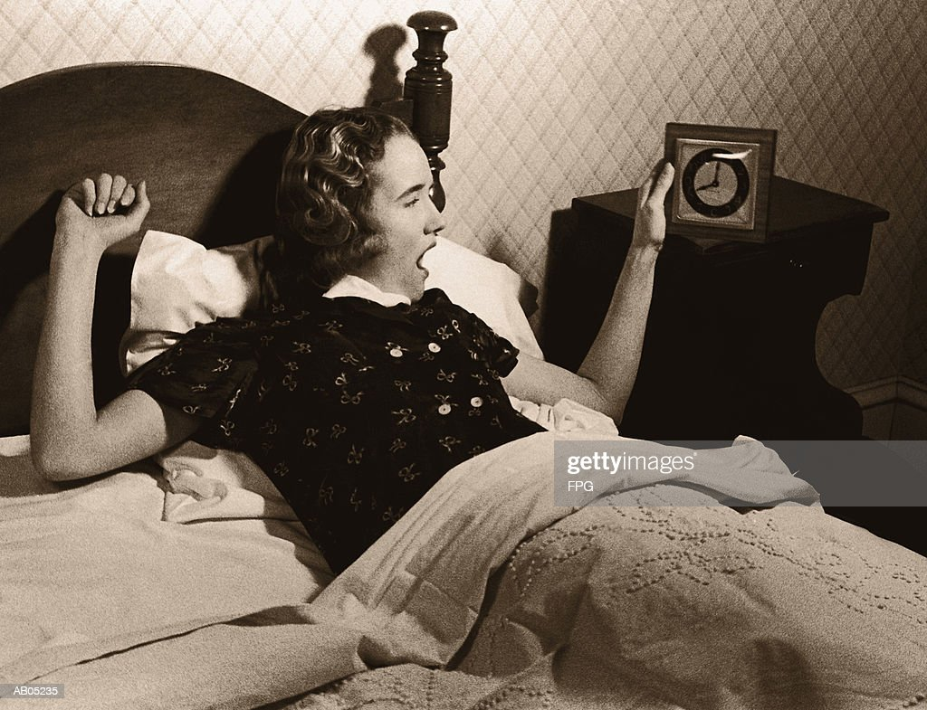 WOMAN IN BED YAWNING AND LOOKING AT ALARM CLOCK AS SHE WAKES UP : Stock Photo