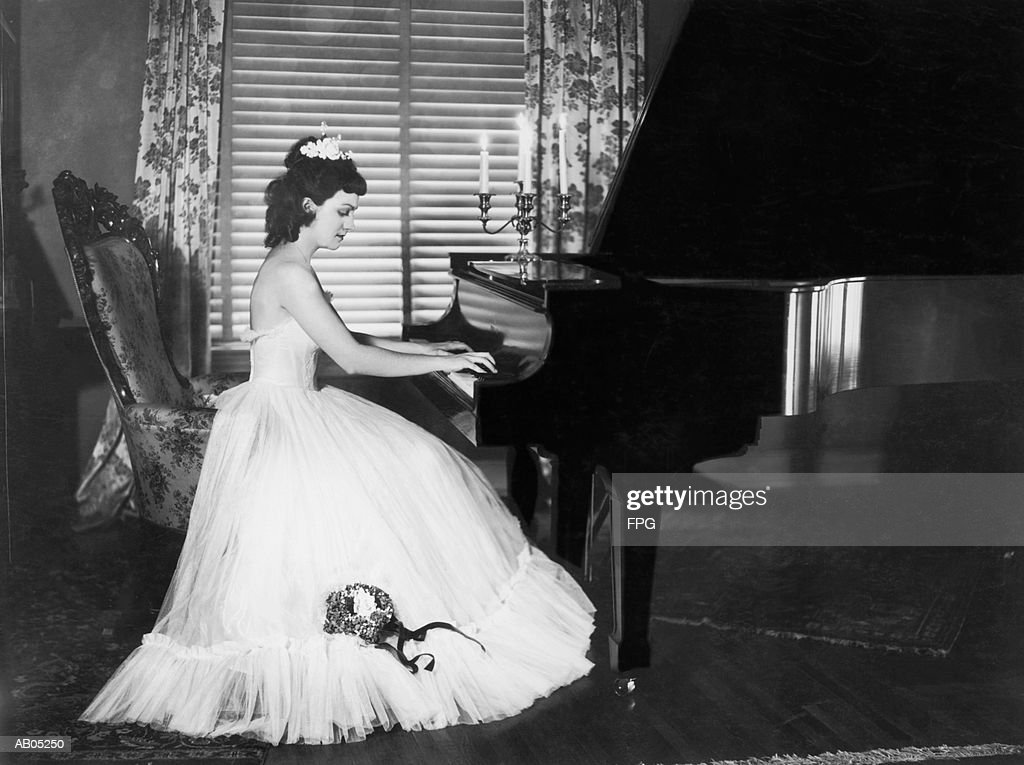WOMAN IN LONG EVENING DRESS PLAYING GRAND PIANO : Stock Photo