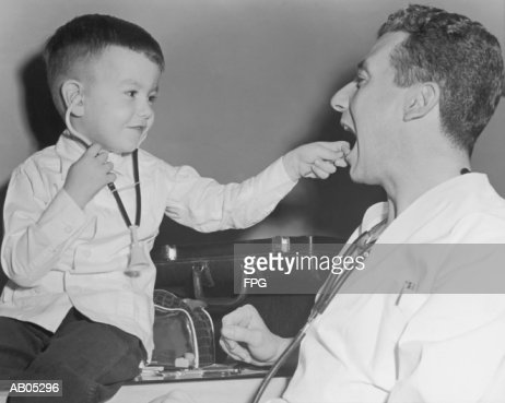 ARCHIVE SHOT / PAEDIATRICIAN WITH BOY HOLDING STETHOSCOPE : Stock Photo