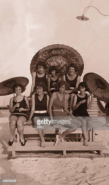 GROUP OF WOMEN IN BATHING SUITS WITH PARASOLS ON BENCH / 1930'S