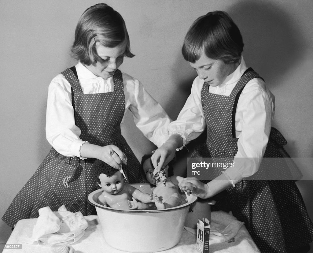 TWIN GIRLS BATHING BABY DOLLS IN SMALL BASIN AT TABLE : Stock Photo