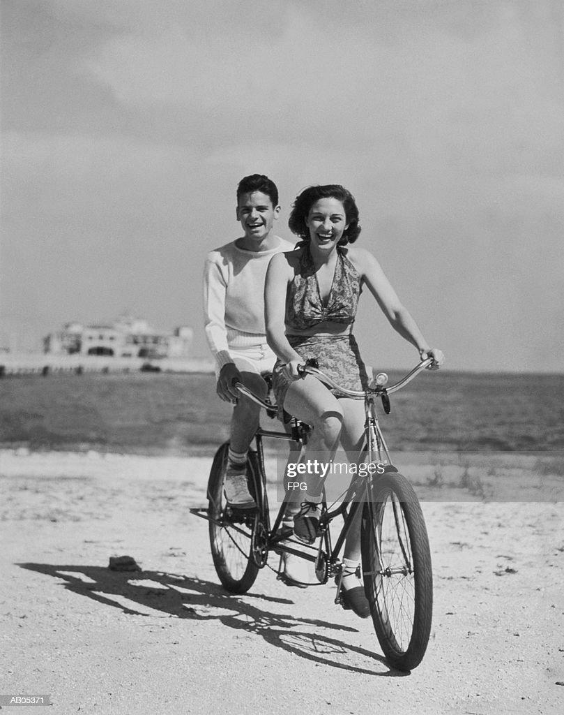 TEENAGE BOY AND GIRL RIDING BIKE ALONG BEACH : Stock Photo