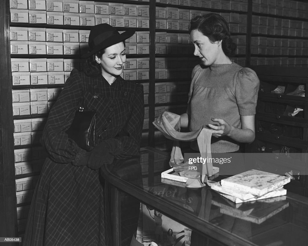 WOMAN TALKING TO SALES ASSISTANT AT COUNTER IN HOSIERY SHOP : Stock Photo