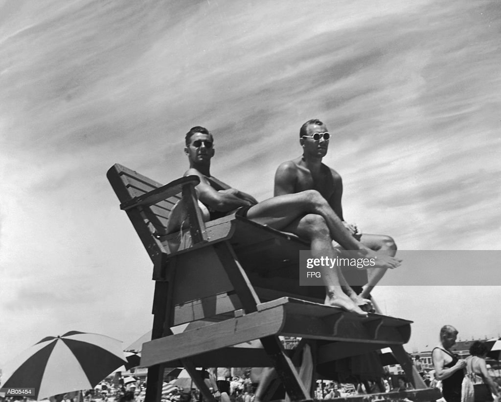 TWO MALE LIFEGUARDS SITTING AT THEIR STATION ON THE BEACH : Stock Photo