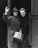 COUPLE WAVING AS THEY BOARD A TRAIN / CIRCA 1930'S