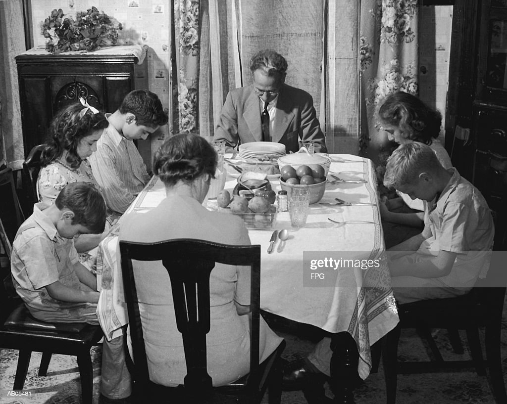 FAMILY SEATED ROUND DINING ROOM TABLE, FATHER SAYING GRACE : Stock Photo