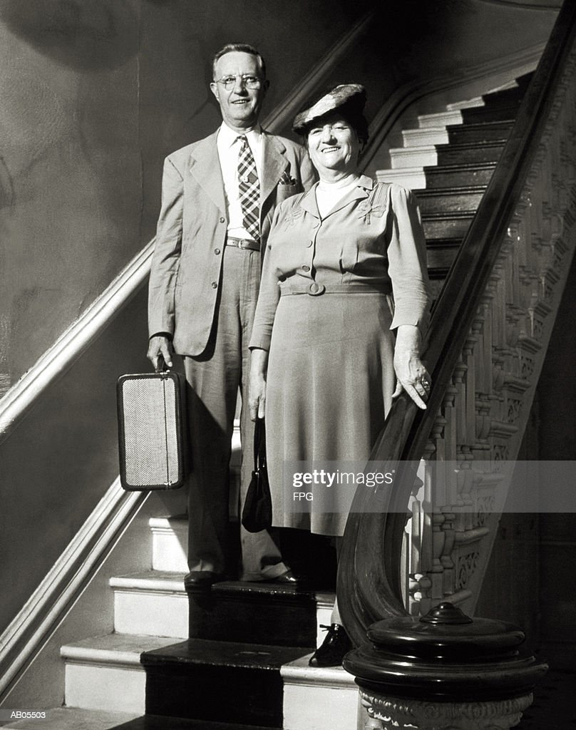 MIDDLE-AGED COUPLE WITH SUITCASE STANDING ON STAIRCASE : Stock Photo