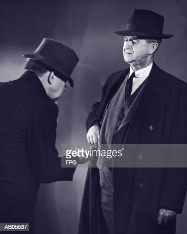 BUSINESSMAN DONATING MONEY TO A POOR MAN BEGGING : Foto stock