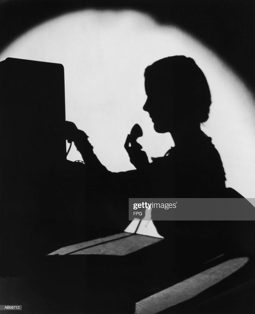 ARCHIVE SHOT / SILHOUETTE OF SWITCHBOARD OPERATOR / INDOORS : Stock Photo