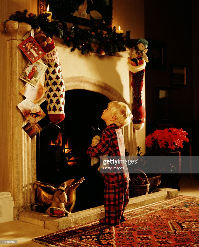 boy in front of fireplace hung with stockings christmas cards