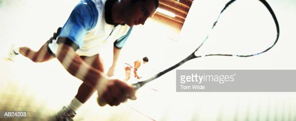 SQUASH PLAYER STRETCHING TO CAMERA / OPPONENT IN BG