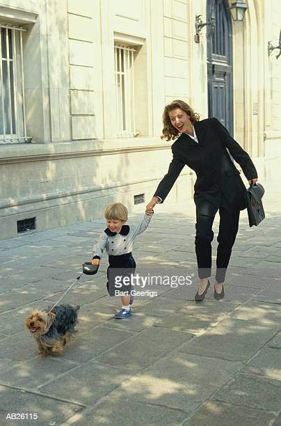 BUSINESSWOMAN OUTDOORS WITH HER LITTLE BOY AND DOG