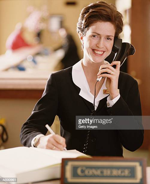 WOMAN AT RECEPTION DESK, USING TELEPHONE AT HOTEL, USA