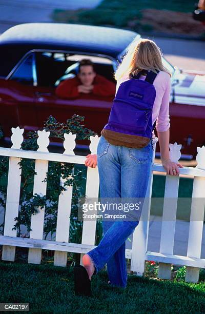 TEEN GIRL BY PICKET FENCE TALKING TO BOY IN CAR