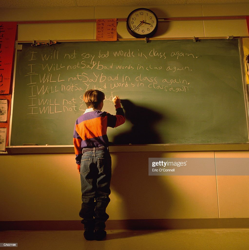 BOY BEING PUNISHED BY WRITING ON BLACKBOARD AFTER SCHOOL