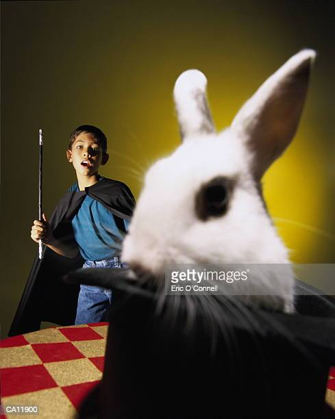 BOY MAGICIAN MAKING RABBIT COME OUT OF HAT