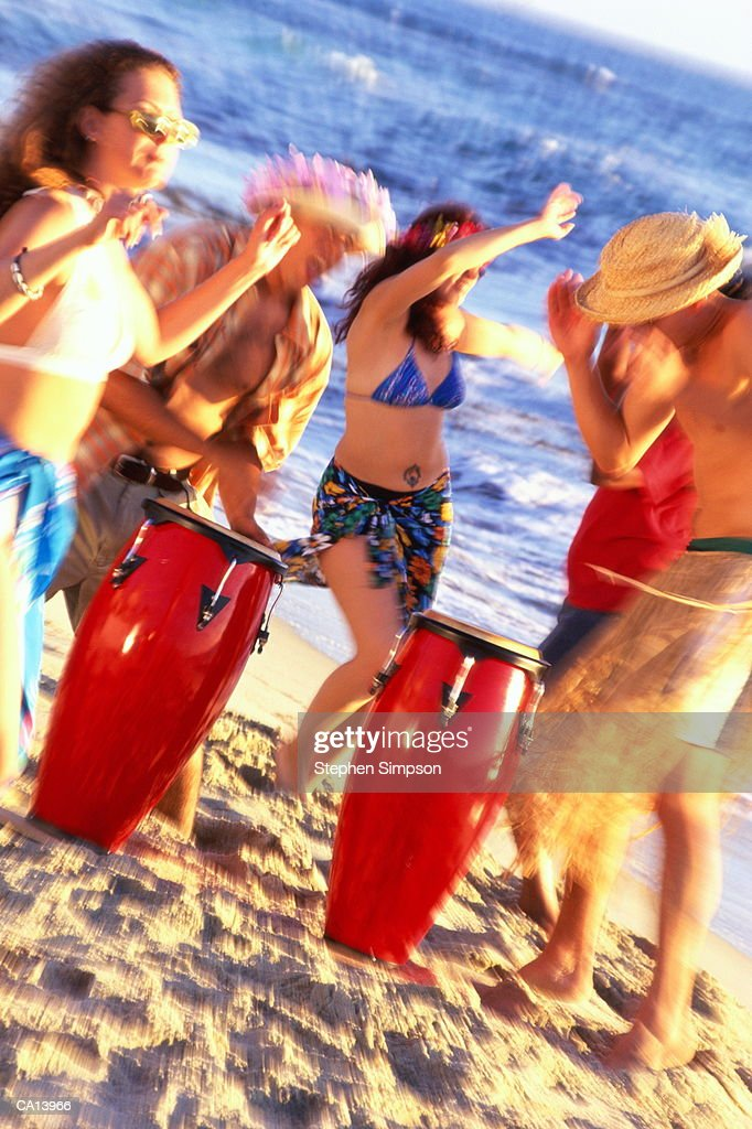 FRIENDS PARTYING AT THE BEACH MEN PLAYING DRUMS : Stock Photo