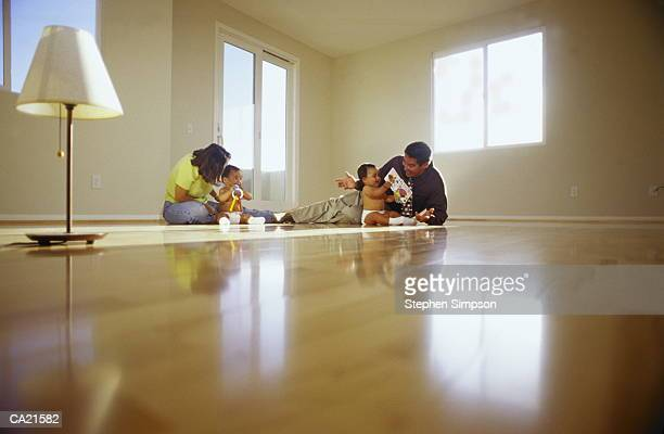 PARENTS WITH TWIN BABY BOYS ON FLOOR IN EMPTY ROOM