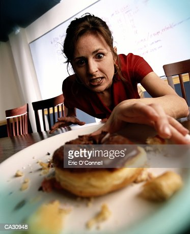 WOMAN REACHING FOR BURGER ONTABLE : Bildbanksbilder