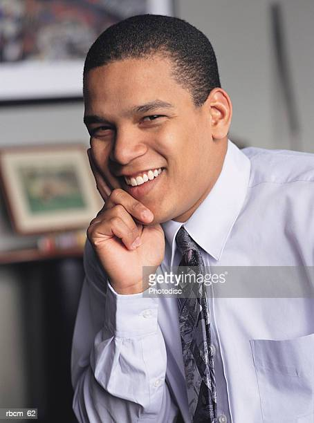 A BLACK BUSINESSMAN IN A BLUE SHIRT AND TIE SMILES WHILE SITTING IN AN OFFICE
