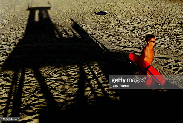 ME0826lifeguard3RL––Newport Beach––Tower guard Chris Esposito carries his rescue bouy while off his tower during the end of his shift watching over a...